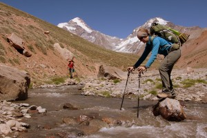 Maura crossing the Relinchos River with Aconcagua looming behind