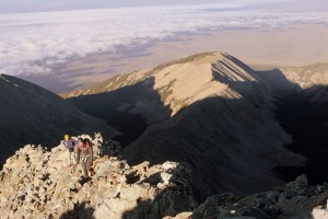 The boys coming up to Little Bear's summit with the beautiful San Luis Valley far below