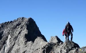 A climber can be seen on the summit of Little Bear Peak behind J & Derek