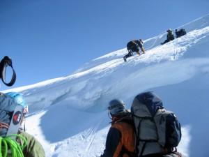 Matt crawling across the tiny snow bridge spanning the crux crevasse at the top of the Tahoma Glacier headwall