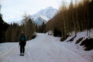 J slowly skiing out the Maroon Creek Road with Pyramid in the distance
